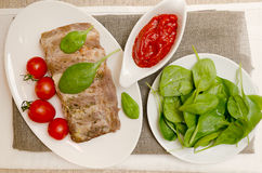 与菜和调味汁的猪排 免版税库存图片