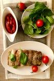 与菜和调味汁的猪排 库存照片