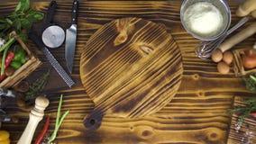 与菜和食物的木桌烹调的顶视图 落在烹调的木板的未加工的鸡内圆角 股票录像