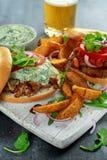 与菜和Tzatziki的可口百吉卷猪肉三明治调味和在白板的油炸物 免版税库存照片