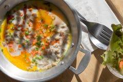 与菜服务的煎蛋卷混合在桌上的热的平底锅在coffe 免版税图库摄影