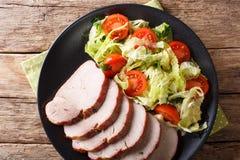 与菜沙拉特写镜头的被烘烤的猪里脊肉在板材 免版税库存照片