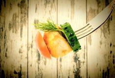 与菜特写镜头的油煎的肉在木葡萄酒背景的一把叉子上 老牌 库存图片