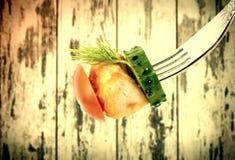 与菜特写镜头的油煎的肉在木葡萄酒背景的一把叉子上 老牌 免版税库存照片