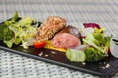 与菜的小牛肉调味汁在黑暗的板材 免版税库存图片