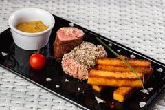 与菜的小牛肉调味汁在黑暗的板材 免版税图库摄影