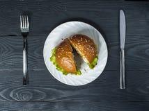 与菜的开胃汉堡包在有叉子的白色在木桌上的板材和刀子 免版税库存图片