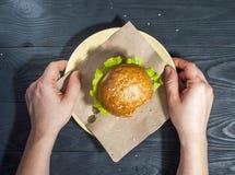 与菜的开胃汉堡包在有叉子的白色在木桌上的板材和刀子 库存图片