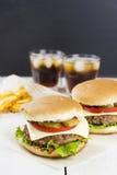 与菜的微型汉堡和肉、炸薯条和饮料在白色木背景 免版税库存照片