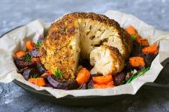 与菜的整个烤花椰菜,健康素食主义者晚餐 免版税图库摄影