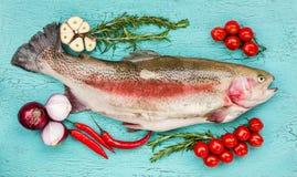 与菜的新鲜的鳟鱼鱼在蓝色木桌上 顶视图 免版税库存照片