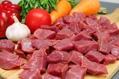 与菜的未加工的切口牛肉在木板材 库存图片
