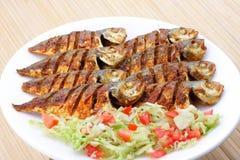 与菜的油煎的鱼。 免版税图库摄影