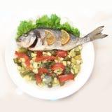 与菜的海鲷鱼在白色板材 免版税图库摄影