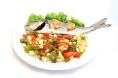 与菜的海鲷鱼在白色板材 免版税库存照片