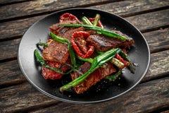 与菜的烤牛肉,春天葱,在板材的芦笋 库存照片