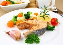 与菜的烤鲑鱼排在白色板材 免版税图库摄影