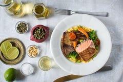 与菜的烤鲑鱼排在白色板材 库存照片