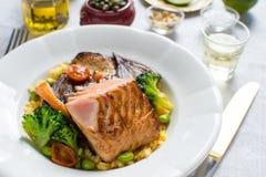与菜的烤鲑鱼排在白色板材 库存图片