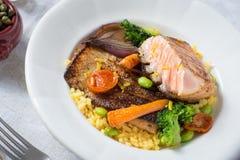 与菜的烤鲑鱼排在白色板材 免版税库存图片