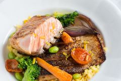 与菜的烤鲑鱼排在白色板材 免版税库存照片