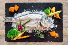 与菜的煮熟的鱼在盐 免版税库存照片