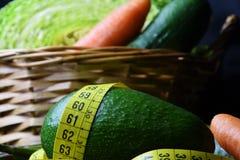 与菜的篮子:圆白菜、鲕梨、黄瓜、芦笋、红萝卜和测量的米 库存图片