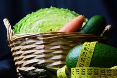 与菜的篮子:圆白菜、鲕梨、黄瓜、芦笋、红萝卜和测量的米 免版税库存图片