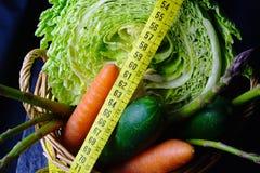 与菜的篮子:圆白菜、鲕梨、黄瓜、芦笋、红萝卜和测量的米 免版税库存照片