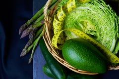 与菜的篮子:圆白菜、鲕梨、黄瓜、芦笋和测量的米 库存图片