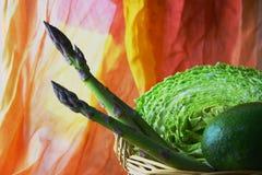 与菜的篮子:圆白菜,鲕梨,在明亮的橙色背景的芦笋 免版税图库摄影