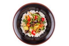 与菜的米在白色背景的一个黑碗 装饰 库存图片