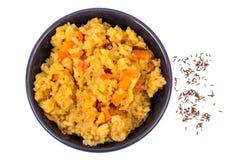 与菜的米在白色背景的黑碗 在视图之上 库存图片