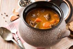与菜的肉炖煮的食物在木桌上的陶瓷罐 免版税库存照片