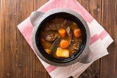 与菜的肉炖煮的食物在木桌上的陶瓷罐 库存图片