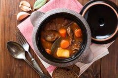 与菜的肉炖煮的食物在木桌上的陶瓷罐 免版税图库摄影