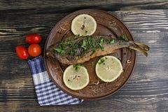 与菜的被烘烤的海鱼在木背景 库存图片