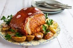 与菜的被烘烤的猪肉火腿在板材和利器侧视图 免版税库存图片