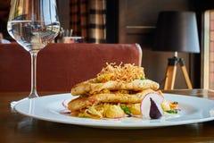 与菜的被烘烤的鳕鱼片在餐馆内部 免版税图库摄影