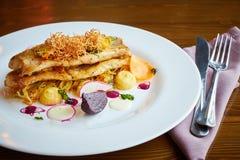 与菜的被烘烤的鳕鱼片在餐馆内部 免版税库存图片