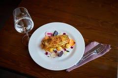 与菜的被烘烤的鳕鱼片在餐馆内部 库存图片