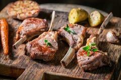 与菜的辣烤羊羔肋骨在老木板条 免版税库存照片
