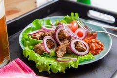 与菜的Chevapchichi在一块蓝色板材 克罗地亚烹调 免版税库存照片