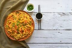与菜的Schezwan面条在一张木桌上的一块板材 r 海达族面条是普遍的印度支那的食谱 免版税图库摄影