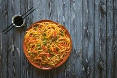 与菜的Schezwan面条在一张木桌上的一块板材 r 海达族面条是普遍的印度支那的食谱 免版税库存照片
