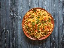 与菜的Schezwan面条在一张木桌上的一块板材 r 海达族面条是普遍的印度支那的食谱 库存图片