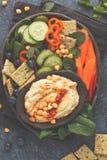 与菜,在黑色的薄脆饼干的自创传统hummus 库存图片