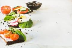 与菜,鸡蛋,鲕梨,蕃茄,在轻的大理石桌上的黑麦面包的不同的三明治 党的开胃菜 库存照片