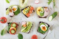 与菜,鸡蛋,鲕梨,蕃茄,在轻的大理石桌上的黑麦面包的不同的三明治 顶视图 党的开胃菜 平面 免版税库存照片