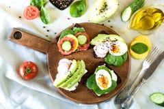 与菜,鸡蛋,鲕梨,蕃茄,在轻的大理石桌上的黑麦面包的不同的三明治 顶视图 党的开胃菜 平面 库存图片